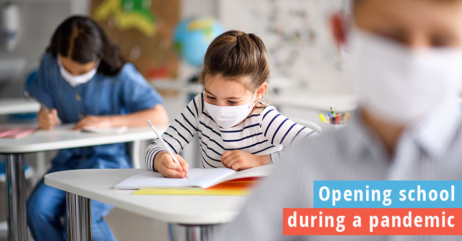 Opening schools during a pandemic, students in masks socially distanced in a fully opened school